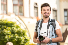 Tourists. Portrait of happy young man, tourists with camera in the city Royalty Free Stock Photos