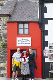 Tourists pose for picture with woman in traditional Welsh costume Stock Photos