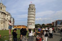 Tourists pose at the tower of Pisa, Italy Stock Images