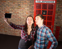 Tourists posing in front of a British phone booth Royalty Free Stock Images