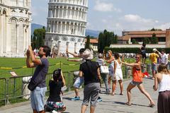 Tourists posing in the leaning tower of Pisa Royalty Free Stock Photos