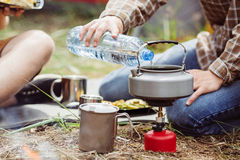Tourists pouring water into the kettle Stock Photo