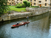 Tourists punting in Cambridge. CAMBRIDGE, UNITED KINGDOM - JULY 18, 2011: Tourists punting in a wooden boat on the river Cam alongside the University of Stock Photography