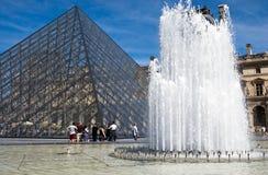 Tourists at Pyramide Louvre Stock Photo