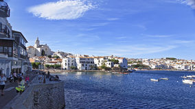 Tourists on the quay and view of Cadaques harbor in summer Royalty Free Stock Images