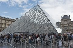 Tourists queue at he Louvre Pyramid royalty free stock photo