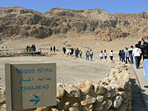 """Tourists in Qumran, Israel. Tourists walking past a signpost """"Trailhead"""" in Qumran, a mountainous desert region, in Israel Stock Images"""