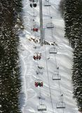 Tourists raiding a chairlift. In a ski resort Royalty Free Stock Image