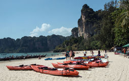 Tourists at Railay Beach March 6,2016,Thailand. Tropical landscape of karst mountains,tourists  enjoying themselves,kayaks on the beach and long-tail boats in Stock Image