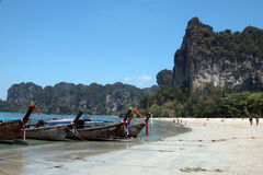 Tourists at Railay Beach March 6,2016,Thailand. Tropical landscape of karst mountains,tourists  enjoying themselves,kayaks on the beach and long-tail boats in Royalty Free Stock Image