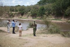 Tourists and ranger at the Mara river Stock Photo