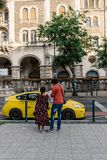 Tourists reading maps near a yellow cab in Budapest Royalty Free Stock Photo