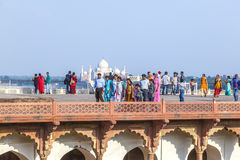 Tourists in the Red Fort in Agra with the Taj Mahal in the background stock image