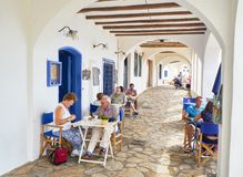 Tourists refreshing on the terrace of a tavern in a gallery of Calella de Palafrugell. Spain. Calella de Palafrugell, Spain - September 15, 2018. Tourists stock images