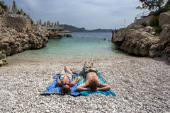 Tourists relax on the rock beach in the Mediterranean seaside town of Kas in Turkey. Royalty Free Stock Photo