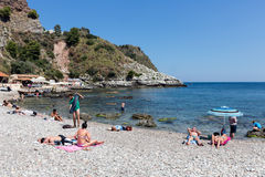Tourists relaxing at the beach of Taormina at Sicily, Italy Royalty Free Stock Image