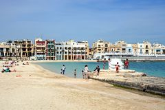 Birzebugga beach, Malta. Tourists relaxing on the beach with waterfront buildings to the rear, Birzebbuga, Malta, Europe Royalty Free Stock Images