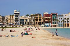 Birzebugga beach, Malta. Tourists relaxing on the beach with waterfront buildings to the rear, Birzebbuga, Malta, Europe Royalty Free Stock Photography