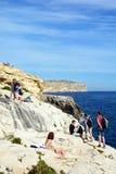 Tourists relaxing at Blue Grotto, Malta. Tourists relaxing on the cliffs at the Blue Grotto Cove, Blue Grotto, Malta, Europe Royalty Free Stock Photos