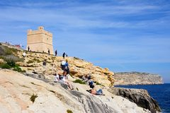 Tourists relaxing by Blue Grotto watchtower, Malta. Tourists relaxing on the cliffs at the Blue Grotto Cove with views towards the watch tower, Blue Grotto Royalty Free Stock Images