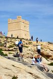 Tourists on the cliffs by Blue Grotto tower, Malta. Tourists relaxing on the cliffs at the Blue Grotto Cove with views towards the watch tower, Blue Grotto Royalty Free Stock Photo