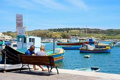 Tourists relaxing on Marsaxlokk quayside, Malta. Traditional Maltese Dghajsa fishing boat in the harbour with a couple sitting on a bench in the foreground Royalty Free Stock Photos