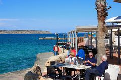 Tourists relaxing at a pavement cafe, Mellieha. Tourists relaxing at a pavement cafe with views across the bay, Mellieha, Malta, Europe Stock Photo