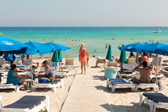 Tourists relaxing on sunbeds on a sandy beach under beach umbrel Royalty Free Stock Images