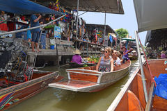 Tourists relaxing on wooden boat at floating market around Bangkok area. European Female Tourists relaxing on wooden boat while gliding through in between two Royalty Free Stock Photography