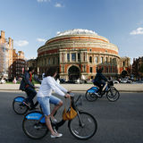 Tourists on rental bike, passing by Royal Albert Hall. London, UK - May 26, 2013 : Tourists on rental bike passing by Royal Albert Hall. London's bicycle sharing Royalty Free Stock Photos