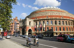 Tourists on rental bike, passing by Royal Albert Hall. London, UK - May 26, 2013 : Tourists on rental bike passing by Royal Albert Hall, public Transport, bus Stock Photo