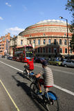 Tourists on rental bike, passing by Royal Albert Hall. London, UK - May 26, 2013 : Tourists on rental bike passing by Royal Albert Hall, public Transport, bus Stock Image