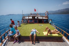 Tourists rest on green deck of  leisure boat trip, Turkey. Royalty Free Stock Photos