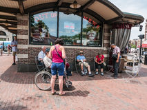 Tourists rest by newsstand in Harvard Square Royalty Free Stock Images