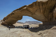 Tourists rest under the shade of the Bridge in Wadi Rum in Jordan. Royalty Free Stock Photos