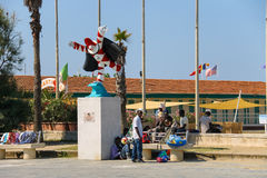 Tourists resting near the statue of Burlamacco. Viareggio, Italy Royalty Free Stock Images