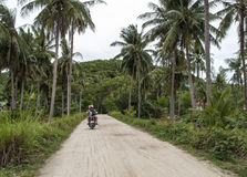 Tourists ridding a scooter on a country road, Thailand Royalty Free Stock Image