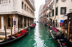 Tourists ride on a gondola in narrow canal and grand canal. Royalty Free Stock Photo