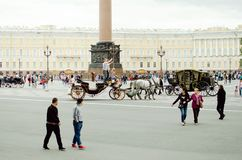 Tourists ride in a horse-drawn carriage on Palace Square in St. Petersburg stock images