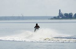 Tourists ride a water motorcycle in the water area of the Sea of Royalty Free Stock Photo