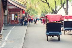 Tourists riding Beijing traditional rickshaw in old China Hutongs in Beijing, China. royalty free stock photos