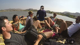 Tourists riding in boat and watching the landscape, closeup. HAMPI, INDIA - 3 FEBRUARY 2015: Tourists riding in boat and watching the landscape, closeup stock video footage