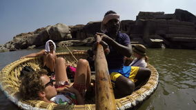 Tourists riding in boat and watching the landscape. HAMPI, INDIA - 3 FEBRUARY 2015: Tourists riding in boat and watching the landscape stock footage