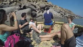 Tourists riding in boat and watching the landscape, timelapse. HAMPI, INDIA - 3 FEBRUARY 2015: Tourists riding in boat and watching the landscape, timelapse stock video footage