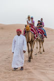 Tourists Riding Camel with Tamer in The Desert of Dubai Royalty Free Stock Photo
