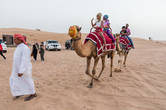 Tourists Riding Camel with Tamer in The Desert of Dubai Royalty Free Stock Photos