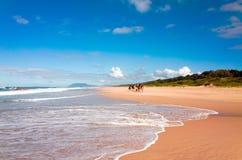 Tourists riding camels on Australian beach Royalty Free Stock Photos