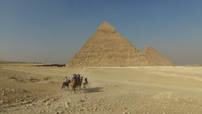 Tourists riding camels at Giza pyramids