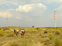 Tourists riding camels near wind turbines in Thar desert during. Camel safari in Rajasthan, India. Thar desert forms a natural boundary between India and stock photography