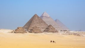 Tourists riding camels at the pyramids at Giza in Egypt stock image